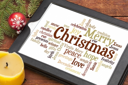 cloud of words or tags related to Christmas on a  digital tablet with a candle and Xmas decorations