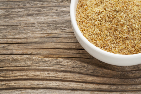 flaxseed: golden flaxseed meal - a ceramic bowl on grained wood background Stock Photo