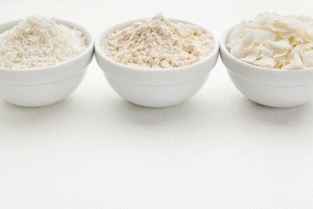 shredded coconut: coconut flour and flakes in three white ceramic bowls on white table cloth