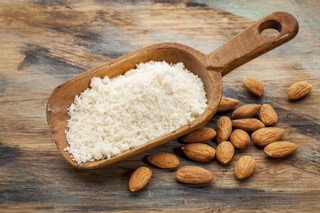 아몬드 가루 단백질 함량이 높고 탄수화물 함량이 적으며 설탕과 글루텐이 적다 - 나뭇결이 고른 목재 배경에 소박한 나무 특종