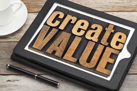 creación de valor - el texto de inspiración en tipografía tipo de cosecha de madera en una tableta digital con una taza de café Foto de archivo