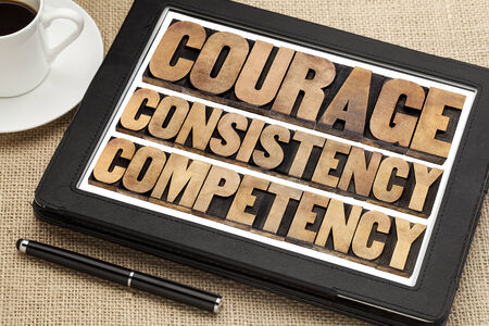 consistency: courage, consistency, competency in vintage letterpress wood type on a digital tablet with a cup of coffee Stock Photo