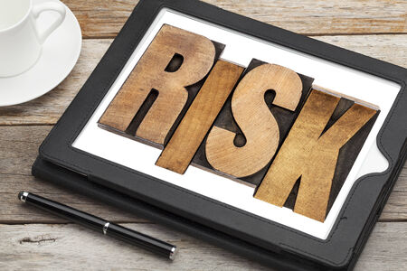 risk - word in letterpress wood type on a digital tablet with a cup of coffee Stock Photo - 24496482