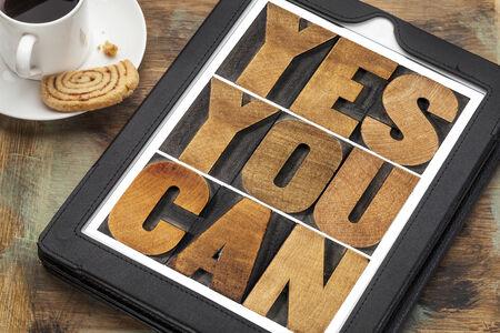 you can: Sí se puede - lema motivacional en una tableta digital con una taza de café