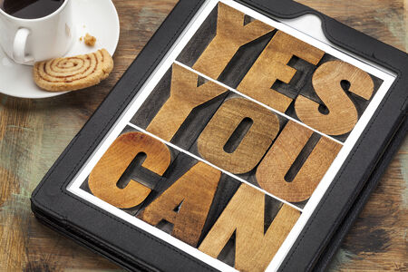 Yes you can - motivational slogan on a digital tablet with a cup of coffee photo