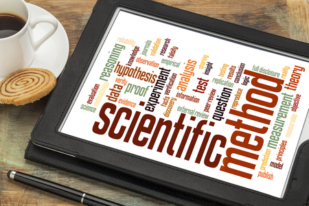 validation: scientific method word cloud on a digital tablet with a cup of coffee