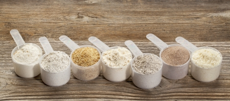 flaxseed: a row of measuring scoops of gluten free flours - almond, coconut, teff, flaxseed meal, whole rice, brown rice, buckwheat Stock Photo