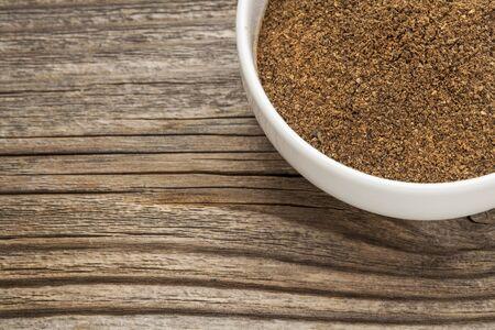 morinda: organic noni fruit powder - a white ceramic bowl on a grained wood