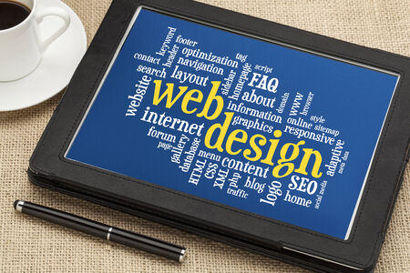 web design word cloud on a  digital tablet with a cup of coffee
