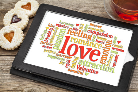 love word cloud on a digital tablet screen with heart cookies and a cup of tea Stock Photo - 24634823