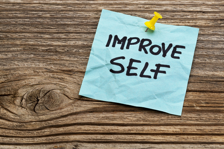 improve self motivational reminder on a sticky note against grained wood Stock Photo - 24634824