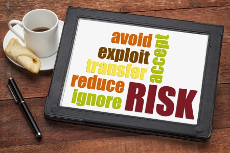 risk management strategies - ignore, accept, avoid, reduce, transfer and exploit - word cloud on a digital tablet Banco de Imagens