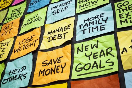 nouvel an: de nouveaux objectifs ou des résolutions années - notes autocollantes de couleurs sur un tableau noir