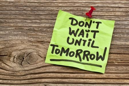 No espere hasta mañana - recordatorio de motivación - escritura a mano en nota pegajosa contra la madera de grano Foto de archivo - 24692882