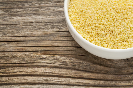 wheat couscous  - a ceramic bowl on grained wood background Stock Photo - 24733541