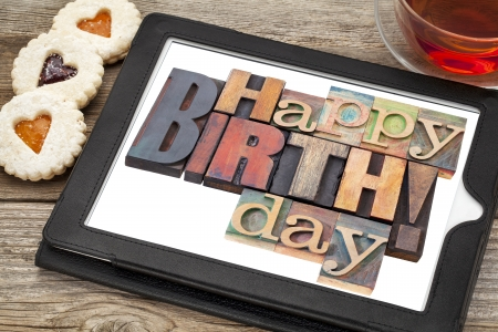 Happy birthday in letterpress wood type on digital tablet with stylus a cup of teat and heart cookies Stock Photo - 24733542