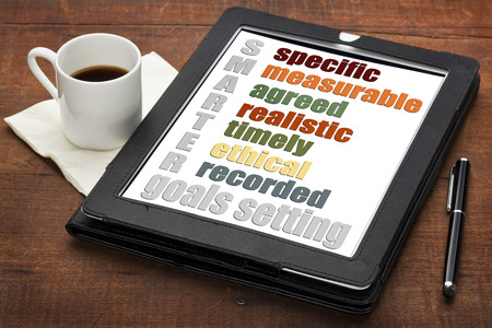 specific: SMARTER (specific, measurable, agreed, realistic, timely, ehtical,  recorded) goal setting concept  on a digital tablet computer with  espresso coffee