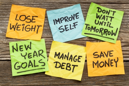 debt goals: New Year goals or resolutions - handwriting on sticky notes against grained wood Stock Photo