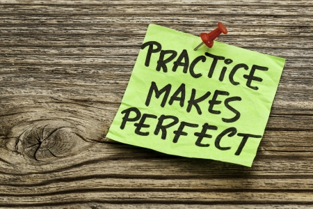 stocky: practice makes perfect - a motivational reminder on a green stocky note against grained wood Stock Photo