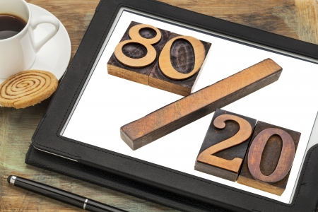 Pareto principle or eighty-twenty rule represented in wood letterpress printing blocks on a digital tablet screen photo