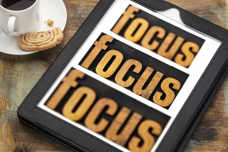 focus word in and out of focus  - text in vintage letterpress wood type on a digital tablet with a cup of coffee Stock Photo - 24876761