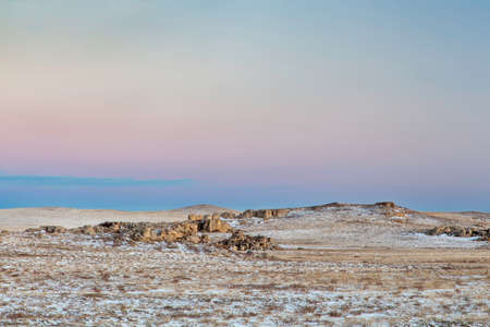 calm winter dusk over prairie in northern Colorado with rock outcropping near Natural Fort geological landmark Stock Photo - 24959902