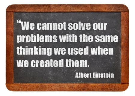 cotizacion: No podemos resolver nuestros problemas con el mismo pensamiento que usamos cuando los creamos - una cita de Albert Einstein - blanco texto tiza en una pizarra pizarra de la vendimia