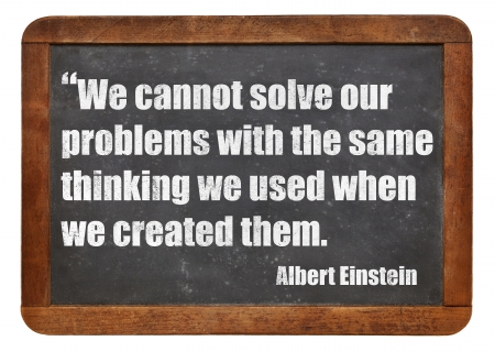 einstein: We cannot solve our problems with the same thinking we used when we created them  - a quote from Albert Einstein - white chalk text  on a vintage slate blackboard