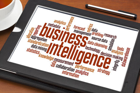 business intelligence word cloud on a digital tablet with a cup of tea