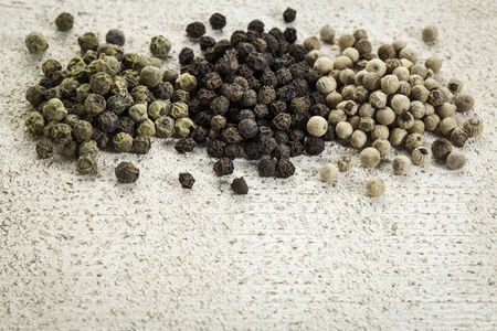green, black and white peppercorns on painted grunge wood background Stock Photo - 24985545