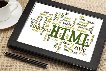 html: html (hypertext markup language) word cloud on a digital tablet with a cup of coffee
