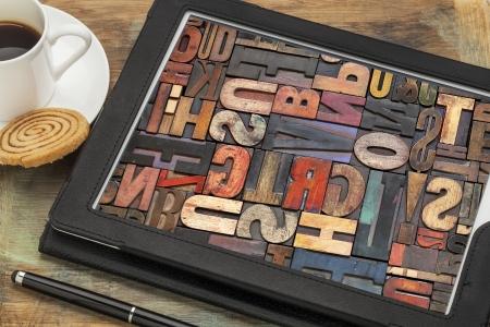 タイポグラフィ コンセプト - コーヒーのカップを持つデジタル タブレット画面上ビンテージ活版木材の種類のアルファベットの抽象的な