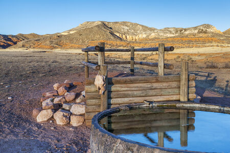 reservoir: cattle watering hole in Red Mountain Open Space, semi desert landscape in northern Colorado near Wyoming border, late summer, reservoir fabricated from old giant tire Stock Photo