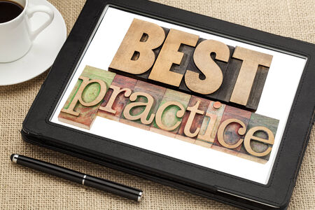 best practices: best practice - isolated words in vintage letterpress wood type on digital tablet screen with a cup of coffee Stock Photo