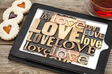 love word abstract - in vintage letterpress wood type printing blocks on a digital tablet with cup of tea and heart cookies photo