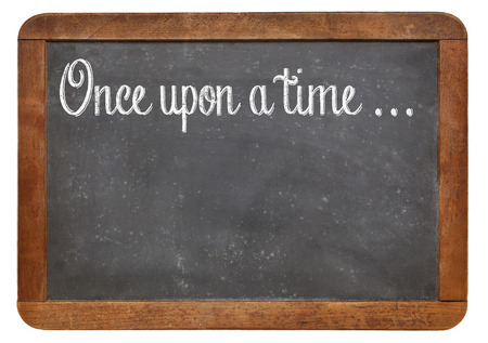 once: Once upon a time - a phrase for opening oral narratives, story or fairytale handwritten with white chalk on blackboard, copy space below Stock Photo