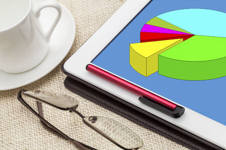 colorful pie chart on digital tablet with a cup of coffee and glasses