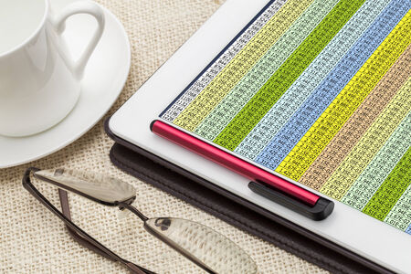 data spreadsheet on a digital tablet with a cup of coffee and reading glasses
