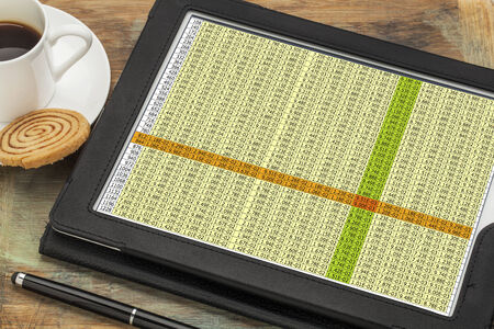 data spreadsheet on a digital tablet with a cup of coffee