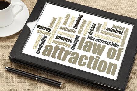 wet van aantrekking woord wolk op een digitale tablet met een kopje koffie Stockfoto