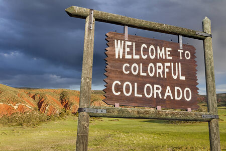 colorado state: welcome to colorful Colorado roadside wooden sign with red sandstone cliff in background Stock Photo