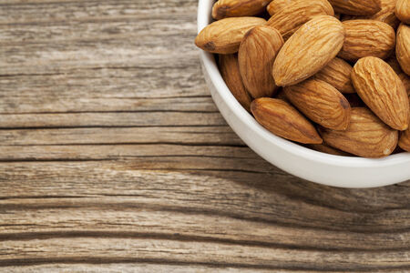 grained: almonds in ceramic bowl on grained wood background