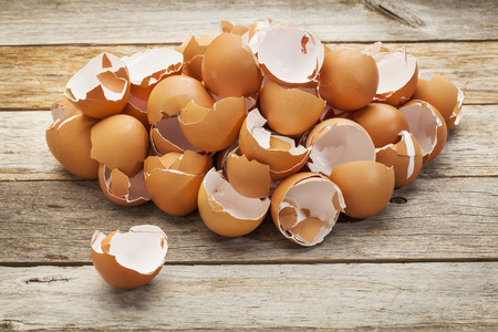 cracked egg: a pile of broken  empty brown chicken eggshells on a rustic wooden table