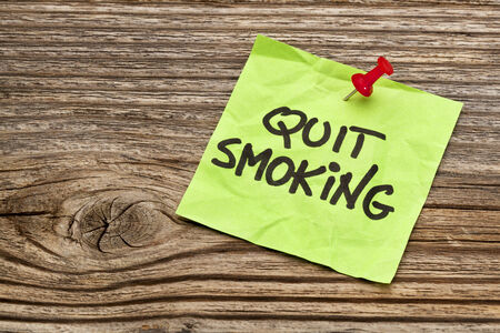 quit smoking: quit smoking reminder note against grained weathered wood