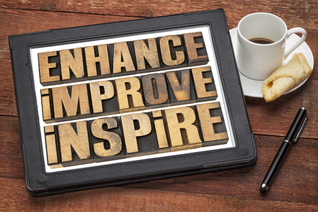 enhance, improve, inspire - a collage of motivational word in vintage letterpress wood type on a digital tablet photo