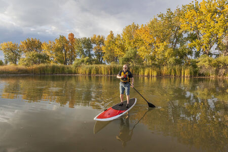 paddler: senior male paddler enjoying workout on stand up paddleboard (SUP), calm lake in Colorado, fall colors Stock Photo