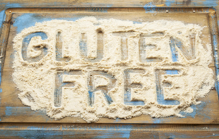 celiac disease: gluten free words written  in coconut  flour on a wooden board