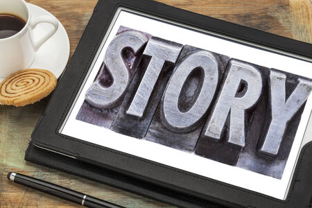 narration: story  - a word in grunge letterpress metal type on a  digital tablet with a cup of coffee Stock Photo