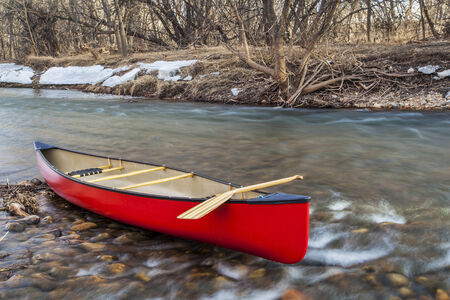 red canoe with a wooden paddle on river shore in winter or early spring