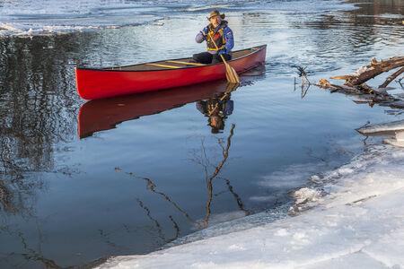 cache la poudre river: a senior male paddling a red canoe in winter
